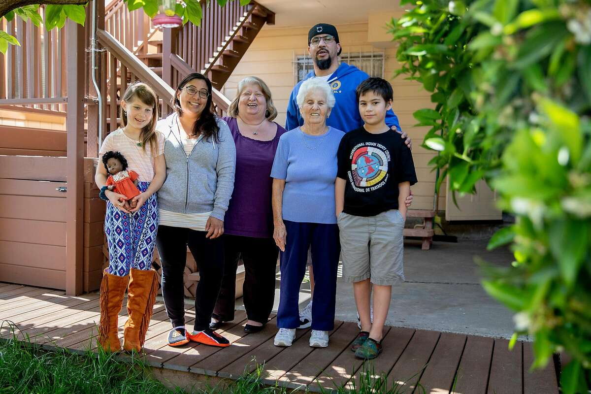 (From left) Celina Gomes' daughter Naima Sutton, 8, Celina Gomes, mother Mary Gomes, grandmother Theresa Vella, brother Dominic Gomes and son Walt Sutton, 10, pose for a portrait in the backyard of Theresa's home in San Francisco, Calif. Saturday, April 18, 2020. The four generations of family live in three homes next door to one another and are sheltering-in-place as a group.