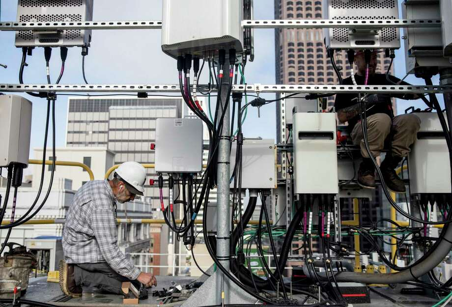 Technicians Tim Felker (left) and Grant Poncy lay the infrastructure for AT&T's 5G network on top of the historic Argonaut Building in the Financial District of San Francisco, Calif. Thursday, Jan. 10, 2019. Photo: Jessica Christian, Staff / The Chronicle / ONLINE_YES
