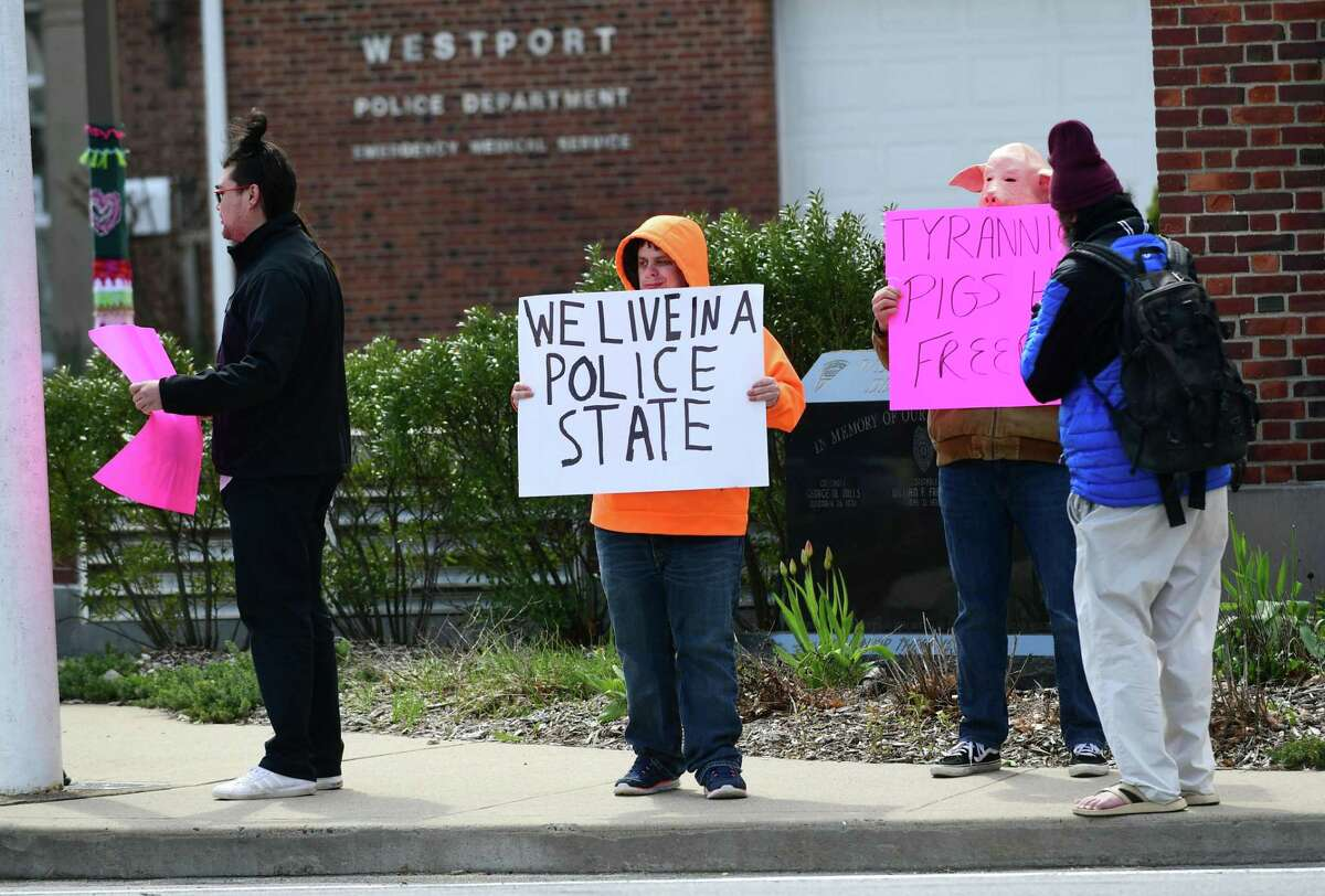 Protestors gather outisde the Westport Police Department Wednesday in Westport. The group was protesting the use of drones by the department to surveil residents diagnosed with coronavirus.