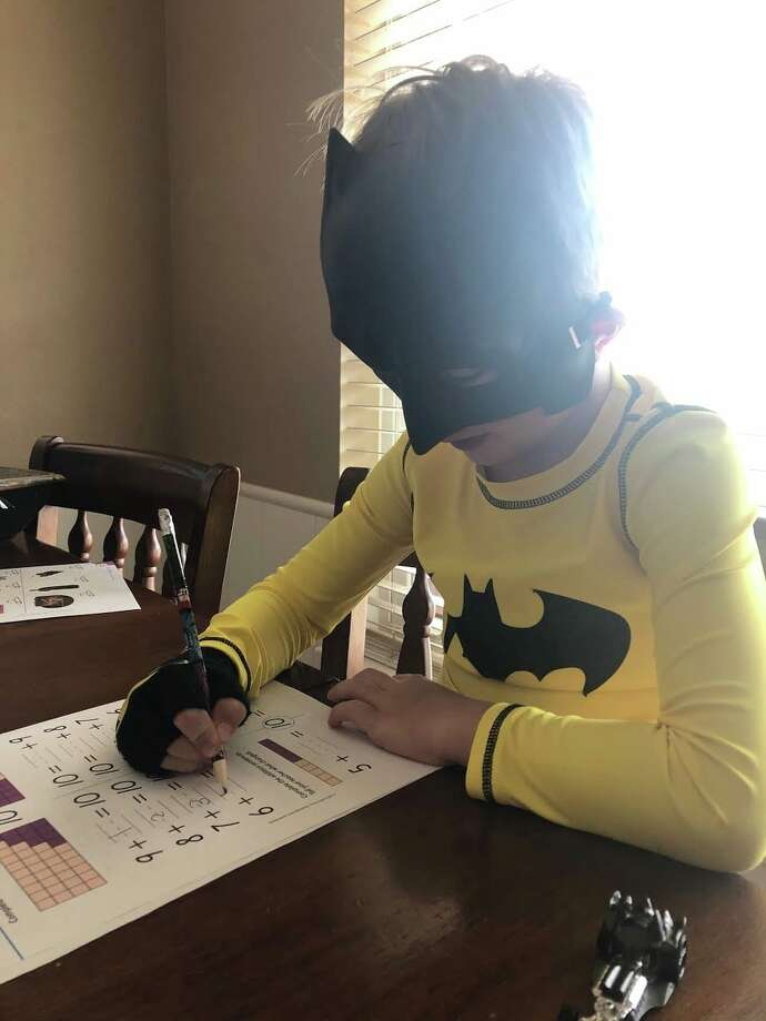 A Plainview Christian Academy takes on school work while wearing a Batman mask. Photo: Courtesy Photo/PCA