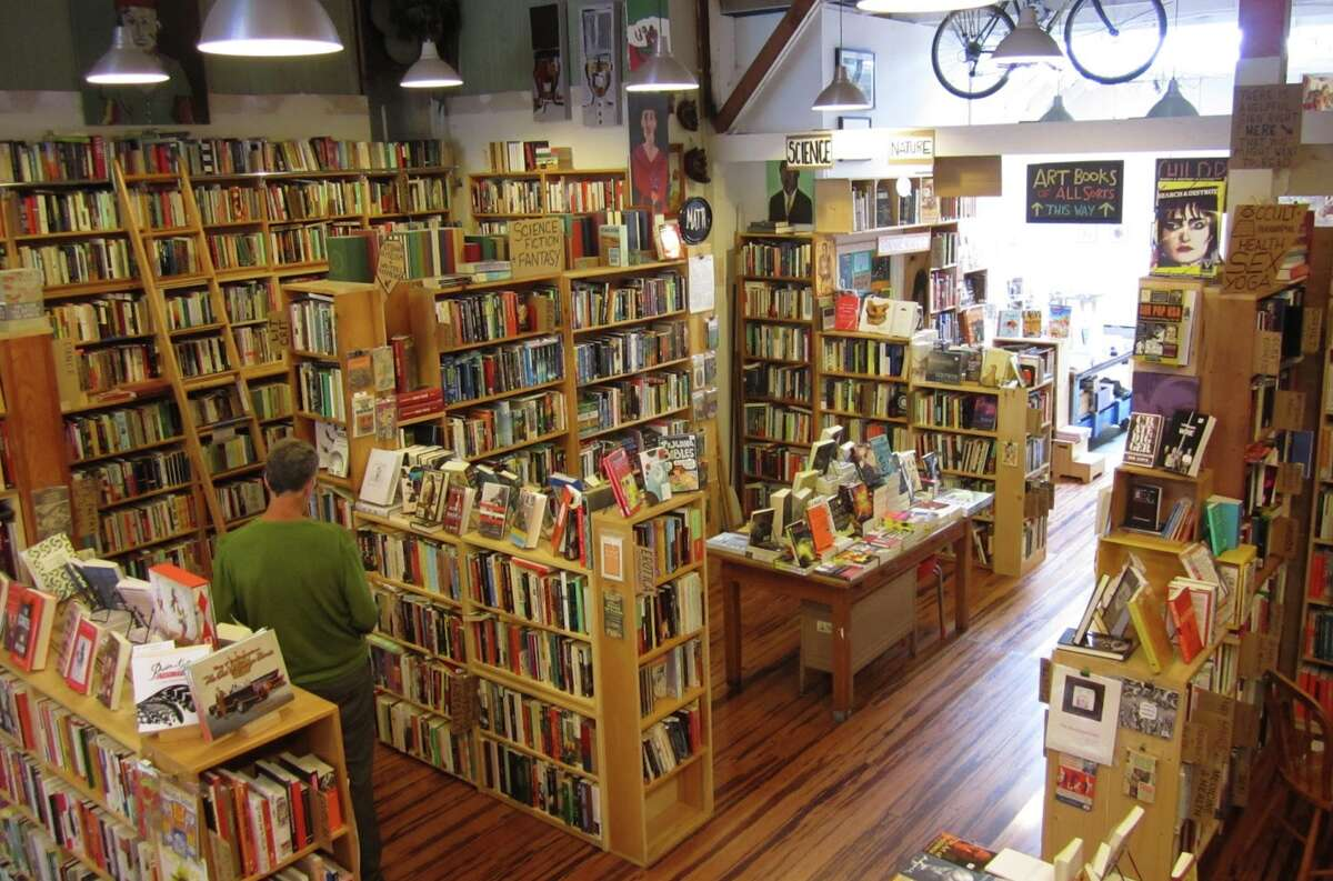 A reader browses the material at Alley Cat Books, an independent bookshop, art gallery and screening space in the Mission District that may not re-open due to the pandemic.