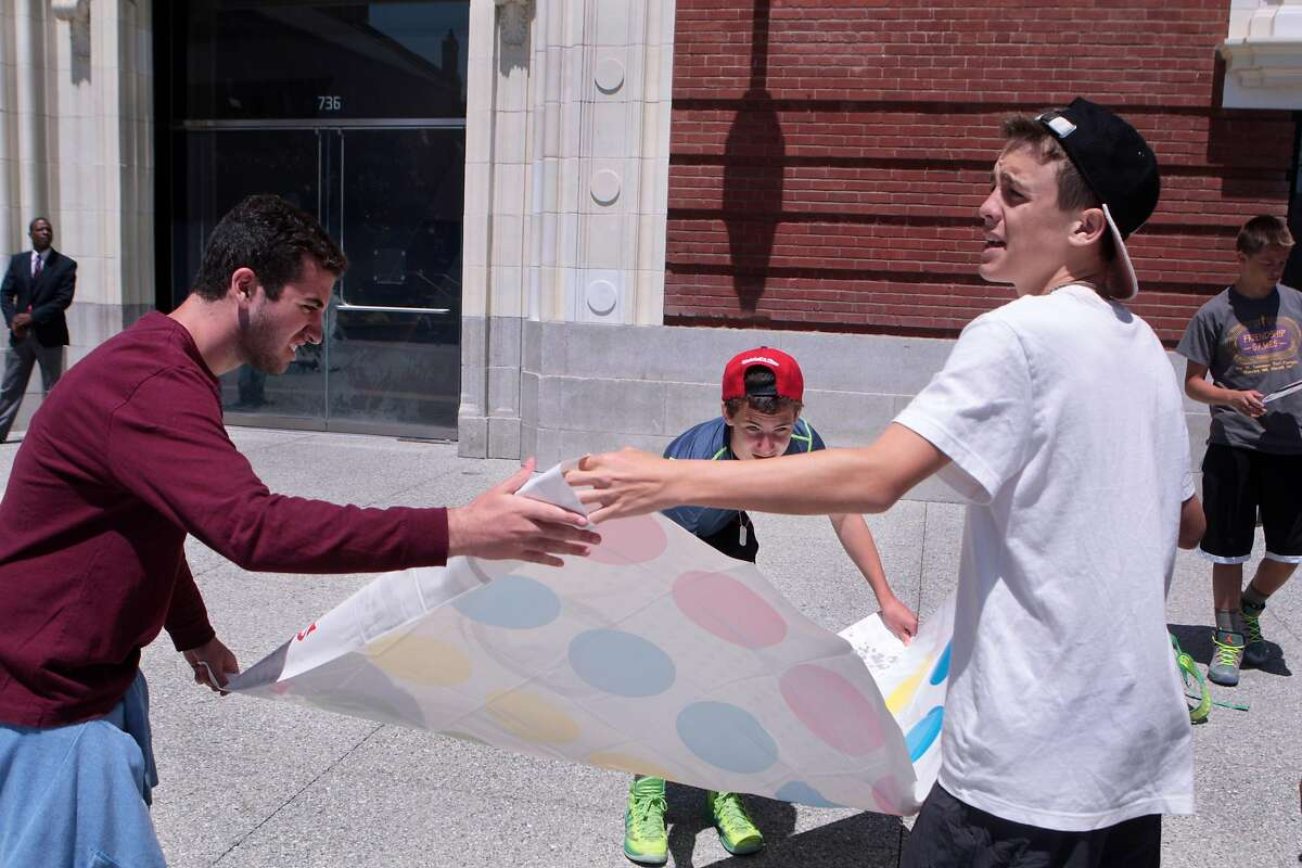 Teens from a Pennsylvania summer camp lay out the mat to play Twister during a lunchtime board games event at Jessie Square Plaza at the Contemporary Jewish Museum in San Francisco, Calif. on Tuesday, July 8, 2014. The event will take place on Tuesdays July 15, 22, 29 and August 12, 19 and 26 from noon to 1 p.m.