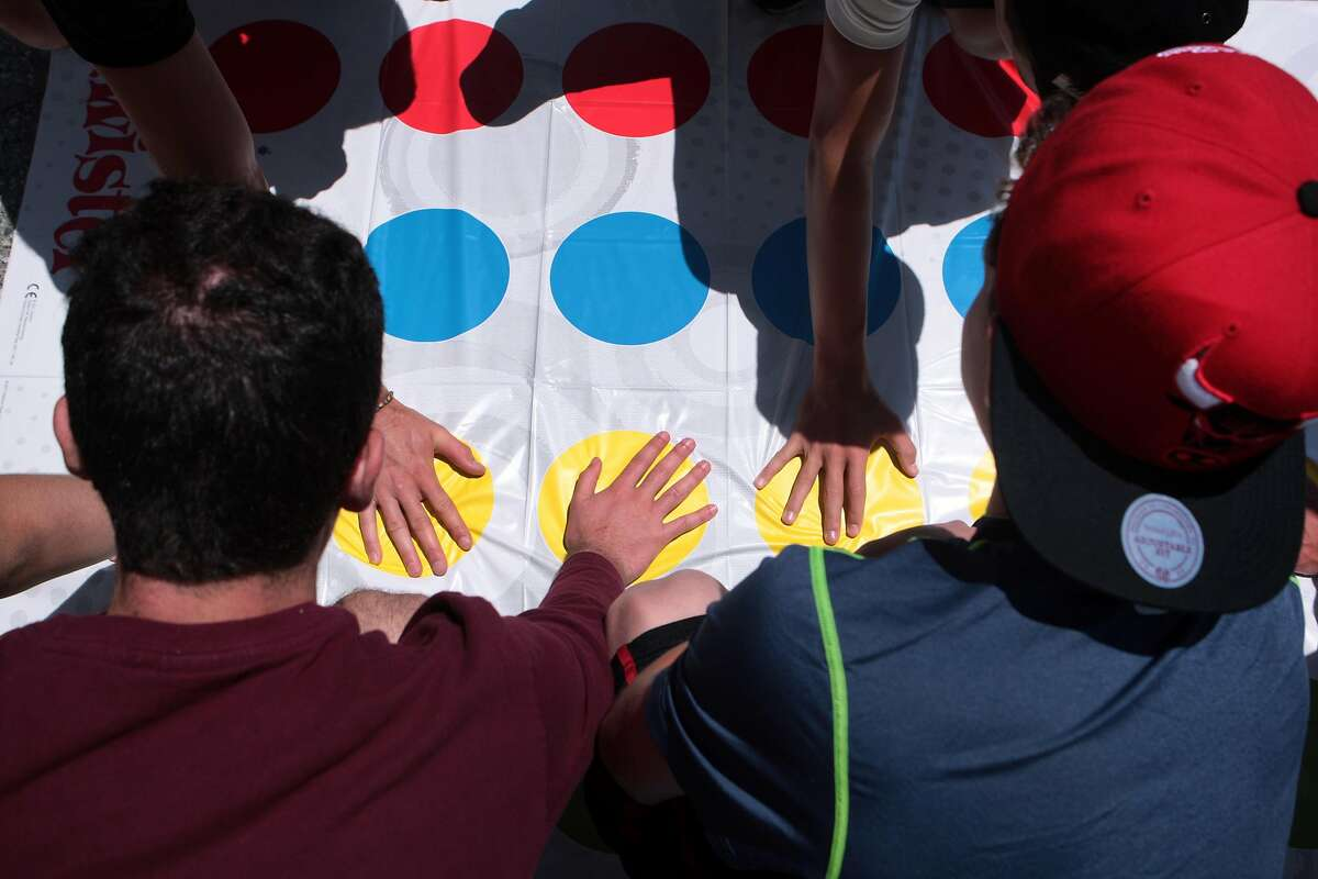 Teens from a Pennsylvania summer camp play Twister during a lunchtime board games event at Jessie Square Plaza at the Contemporary Jewish Museum in San Francisco, Calif. on Tuesday, July 8, 2014. The event will take place on Tuesdays July 15, 22, 29 and August 12, 19 and 26 from noon to 1 p.m.