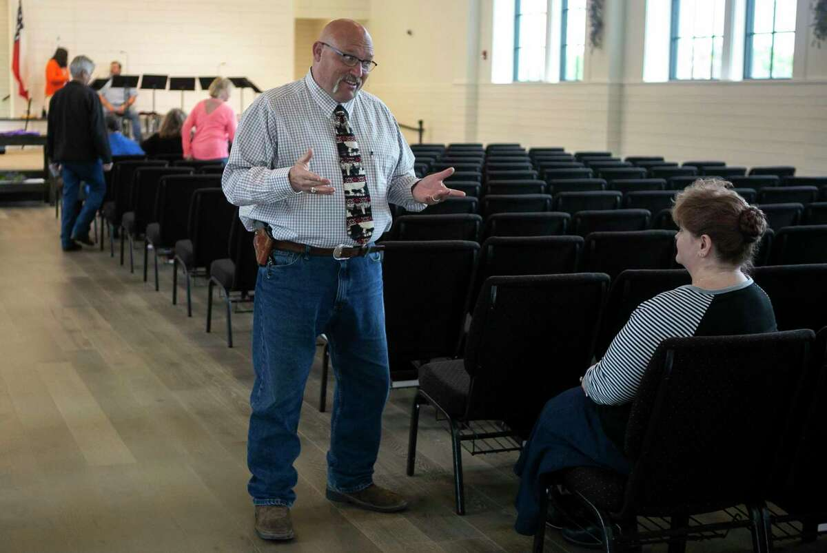 """Pastor Frank Pomery talks with visitor Charlene Cummings before Sunday morning service at First Baptist Church in Sutherland Springs, Texas, April 5, 2020. Cummings is visiting First Baptist because her home church is closed due to COVID-19 and wanted to worship with other believers in-person. Going to church has been an important part of Cummings' life and healing from the trauma she has survived and the resulting PTSD. """"Church is just as vital (to me) as it was before the virus,"""" she says."""