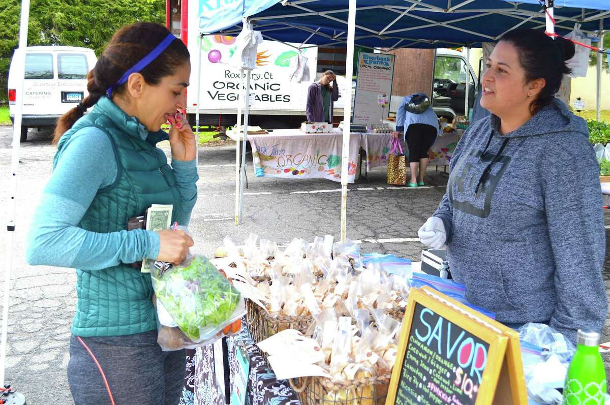 At the opening day of the Farmer's Market, Ladan Tavasoli of New Canaan samples one of Jodi Bulvanoski's cookies from the Thomaston-based at Savor the Difference.
