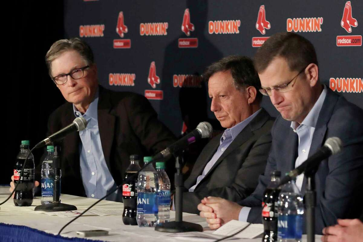 FILE - From left, in a Jan. 15, 2020, file photo, Boston Red Sox owner John Henry, chairman Tom Werner and CEO Sam Kennedy react during a news conference at Fenway Park in Boston. The Boston Red Sox were stripped of their second-round pick in this yeara€™s amateur draft by Major League Baseball for breaking video rules in 2018 and former manager Alex Cora was suspended through the 2020 postseason for his conduct as bench coach with the Houston Astros the previous year. Baseball Commissioner Rob Manfred announced his decision Wednesday, April 22, 2020, concluding Red Sox replay system operator J.T. Watkins used in-game video to revise sign sequences provided to players. (AP Photo/Elise Amendola, File)