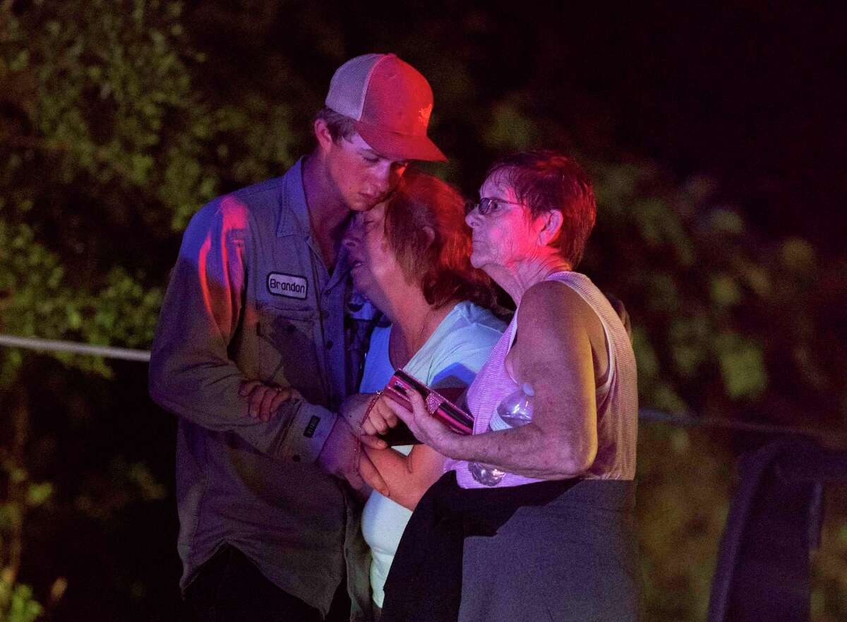 People embrace after an apparent tornado touched down Wednesday, April 22, 2020, in Onalaska, Texas. The storm caused severe damage to homes and other structures, but there were no immediate reports of deaths or serious injuries, said Carrie Miller, a spokeswoman for Polk County Judge Sydney Murphy. (Jason Fochtman/Houston Chronicle via AP)