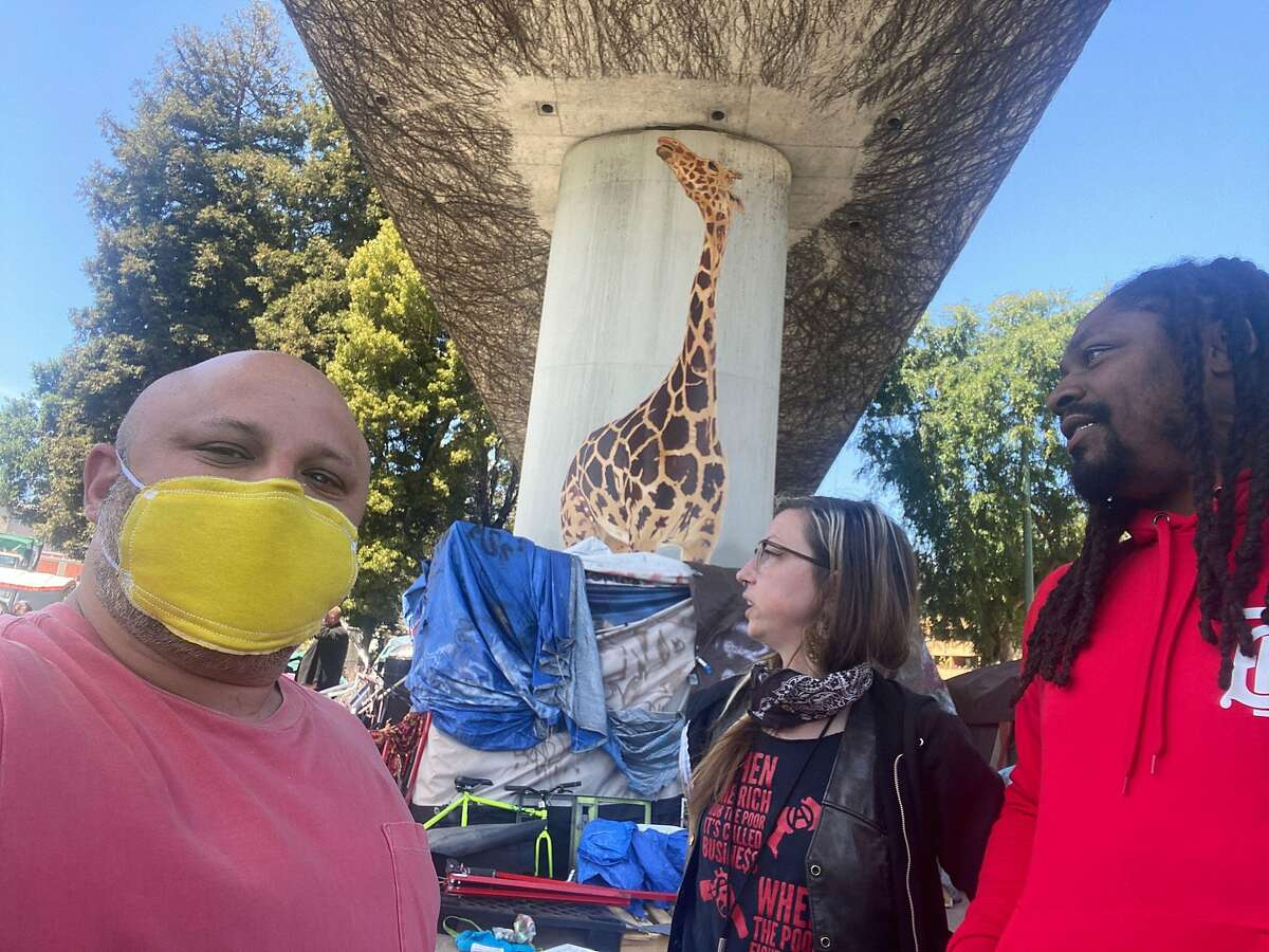 Jeremy Castro, left, Marry How of the Oakland Homeless Youth Alliance and Marshawn Lynch deliver masks on Wednesday, April 22, in Oakland.