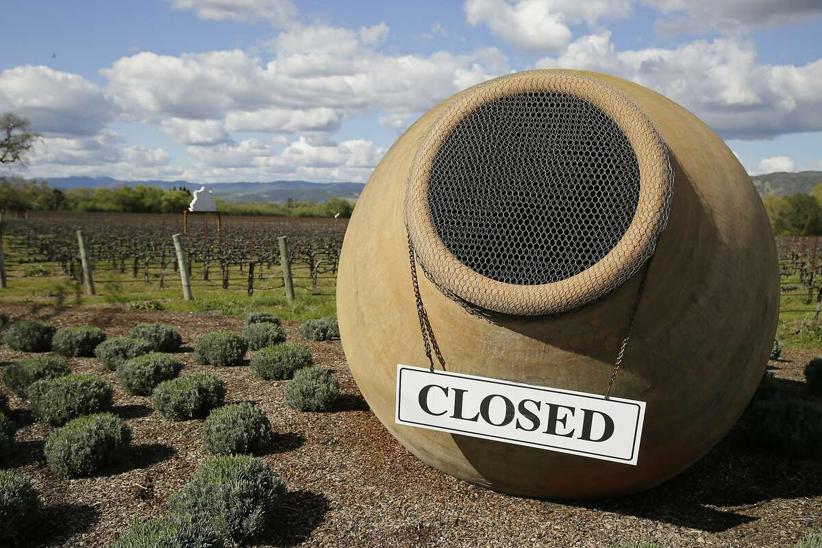 In this photo taken Thursday, March 19, 2020, a closed sign hangs on an oversized amphora outside the driveway and vineyards of the Piazza Del Dotto Winery & Caves in Napa, Calif. Wineries in the Napa Valley are closed due to coronavirus restrictions expect for production, but some allow customers to pick up shipments of wine and for direct purchases. (AP Photo/Eric Risberg)
