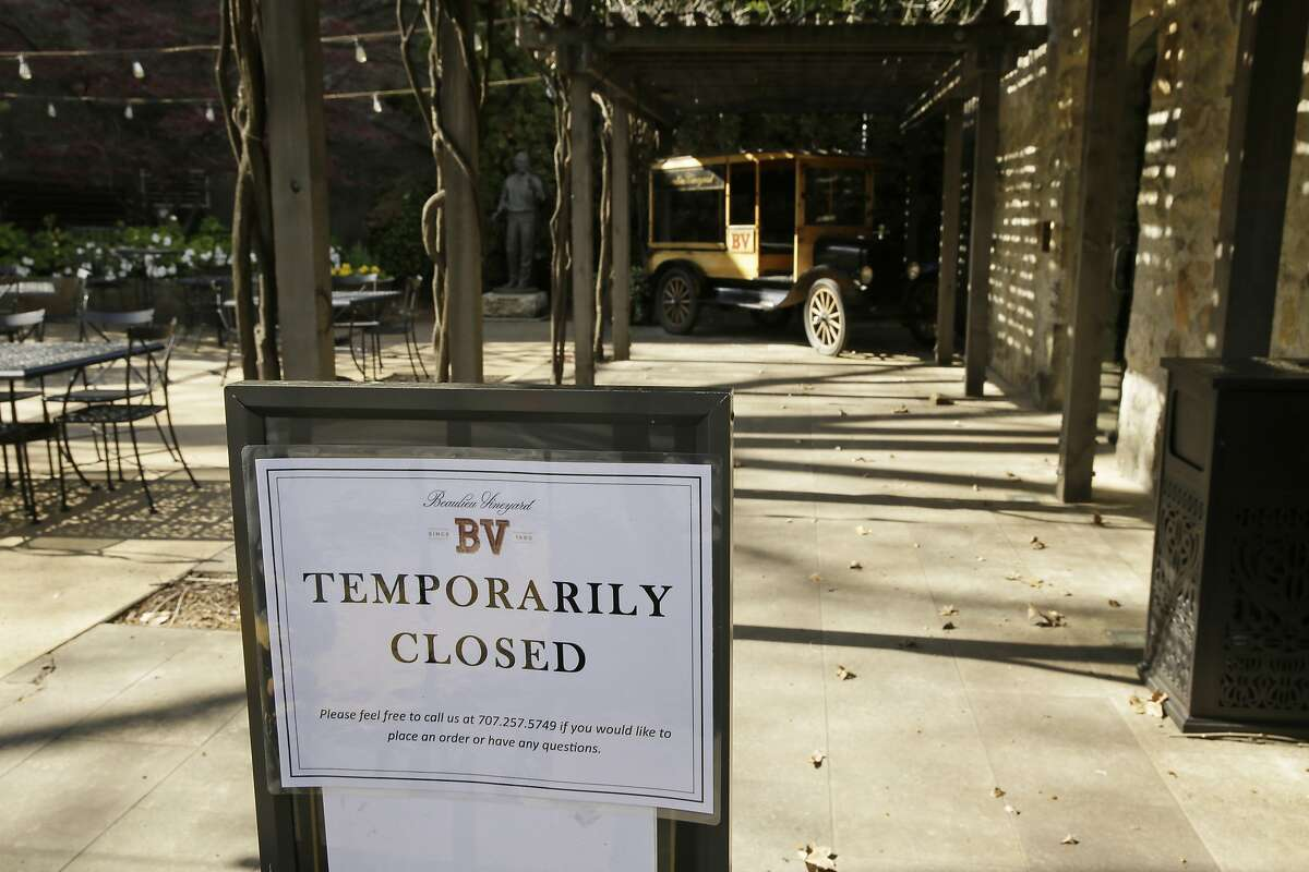 In this photo taken Thursday, March 19, 2020, a temporarily closed sign is posted outside the entrance to the Georges De Latour Reserve Tasting Room at the Beaulieu Vineyard winery in Rutherfod, Calif. Wineries in the Napa Valley are closed due to coronavirus restrictions expect for production, but some allow customers to pick up shipments of wine and for direct purchases. (AP Photo/Eric Risberg)