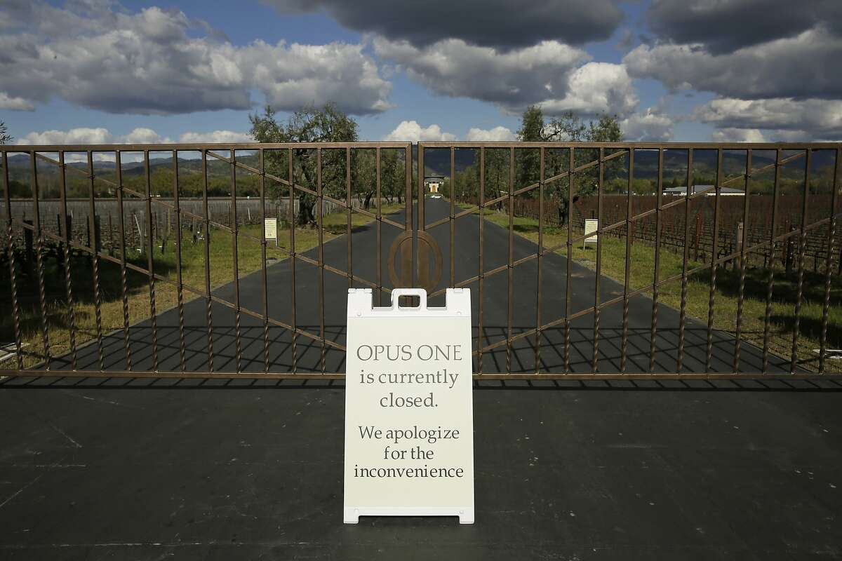 In this photo taken Thursday, March 19, 2020, a closed sign is posted outside the driveway to the Opus One Winery in Oakville, Calif. Wineries in the Napa Valley are closed due to coronavirus restrictions expect for production, but some allow customers to pick up shipments of wine and for direct purchases. (AP Photo/Eric Risberg)