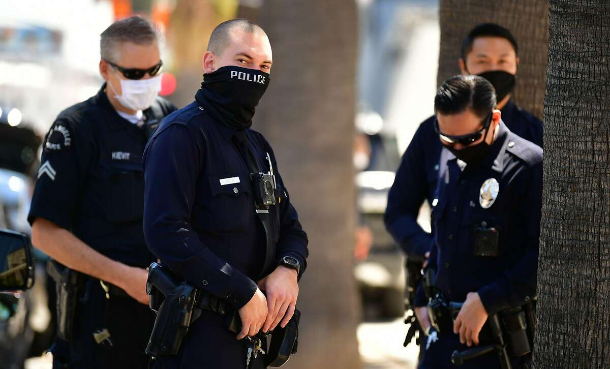 Los Angeles Police Department (LAPD) officers wear facial covering while monitoring an