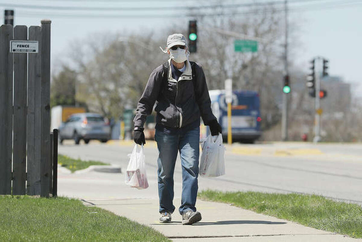 A man wears a mask as he carries shopping bags in Skokie.