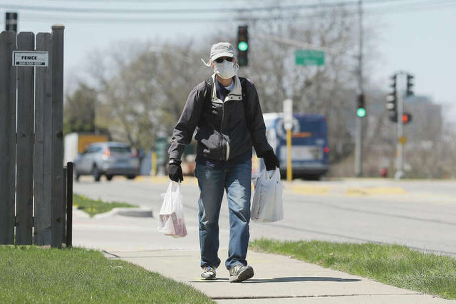 A man wears a mask as he carries shopping bags in Skokie. Photo: Nam Y. Huh | AP