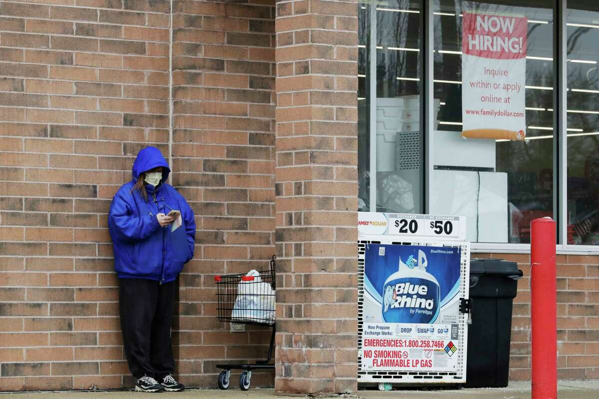 A woman checks her phone as a hiring sign shows at a Family Dollar store in Joliet, Ill., Friday, April 17, 2020. With half-a-million people bounced out of jobs in the past month because of the COVID-19 pandemic, Illinois' unemployment safety net has been stretched to the limit.