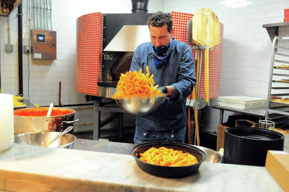 Chef Andrew Testo prepares penne pasta during a free meal distribution at Matto Wine Bar on Bridgeport Ave in Shelton, Conn., on Tuesday Apr. 21, 2020. This is the 7th meal giveaway Chef Testo has hosted, which he does at restaurants around the region. As many as 100 meals were prepared today for the first come first serve event, which was to help anyone who needs a meal during the coronavirus pandemic. Photo: Christian Abraham / Hearst Connecticut Media / Connecticut Post