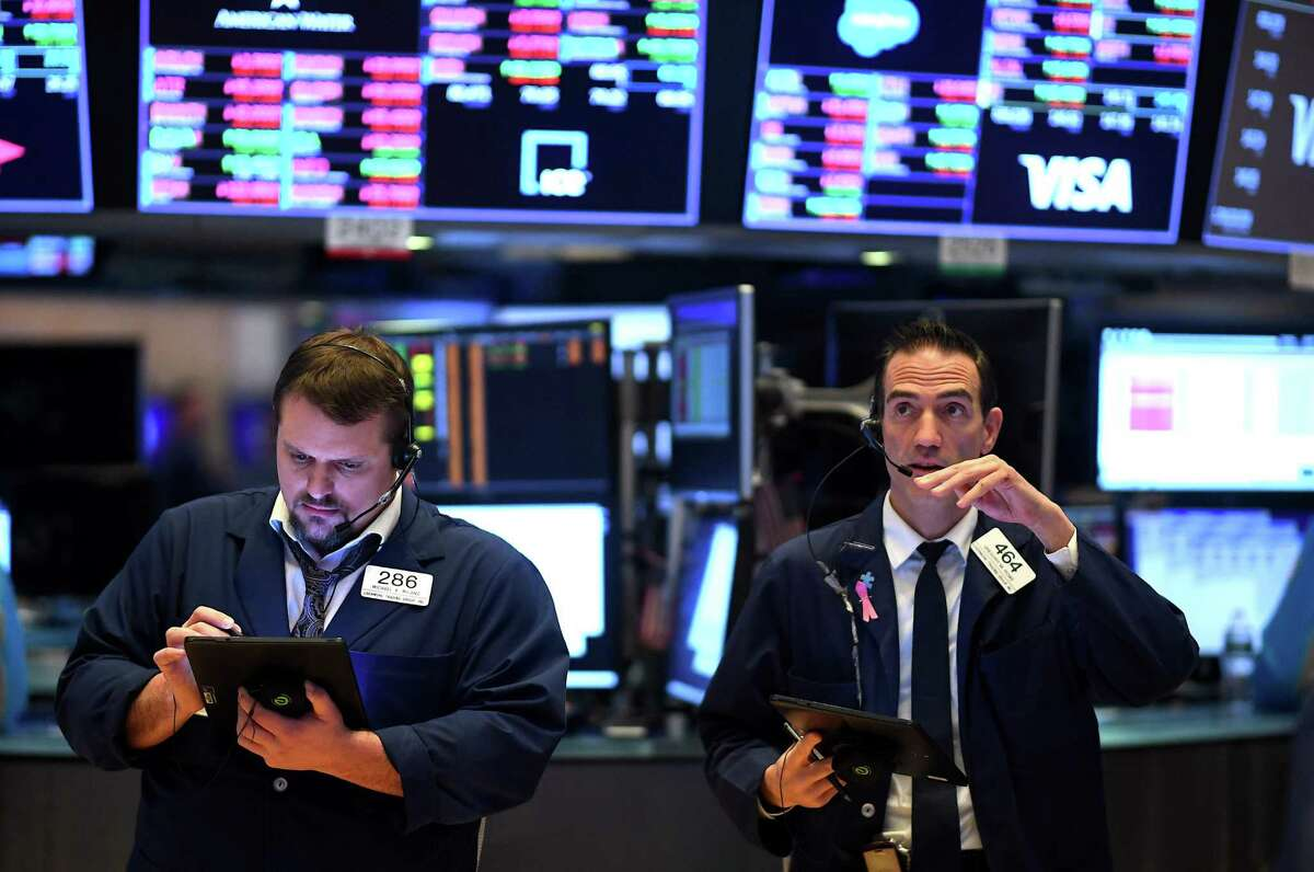 (FILES) In this file photo Traders work during the opening bell at the New York Stock Exchange (NYSE) on March 19, 2020, at Wall Street in New York City. - Wall Street opened lower on April 20, 2020 as traders grappled with a drop in oil prices to 22-year lows as the coronavirus pandemic sapped demand for energy. The Dow Jones Industrial Average was down 1.8 percent to 23,798.01 about 10 minutes into the trading session.The broad-based S&P 500 had declined 1.3 percent to 2,835.08, while the tech-rich Nasdaq had fallen 0.7 percent to 8,588.66. (Photo by Johannes EISELE / AFP) (Photo by JOHANNES EISELE/AFP via Getty Images)