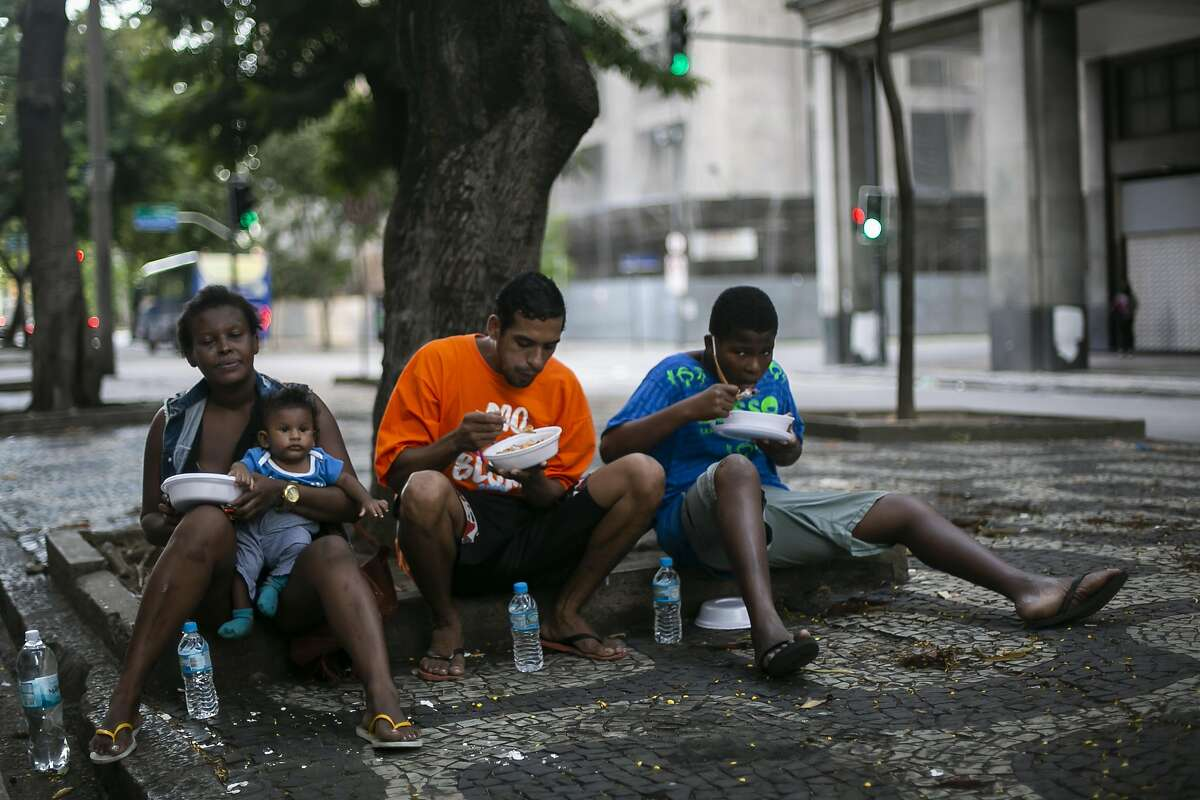 Homeless and unemployed people receive food and water from volunteers of the 'Covid Sem Fome' on April 22, 2020 in Rio de Janeiro, Brazil.