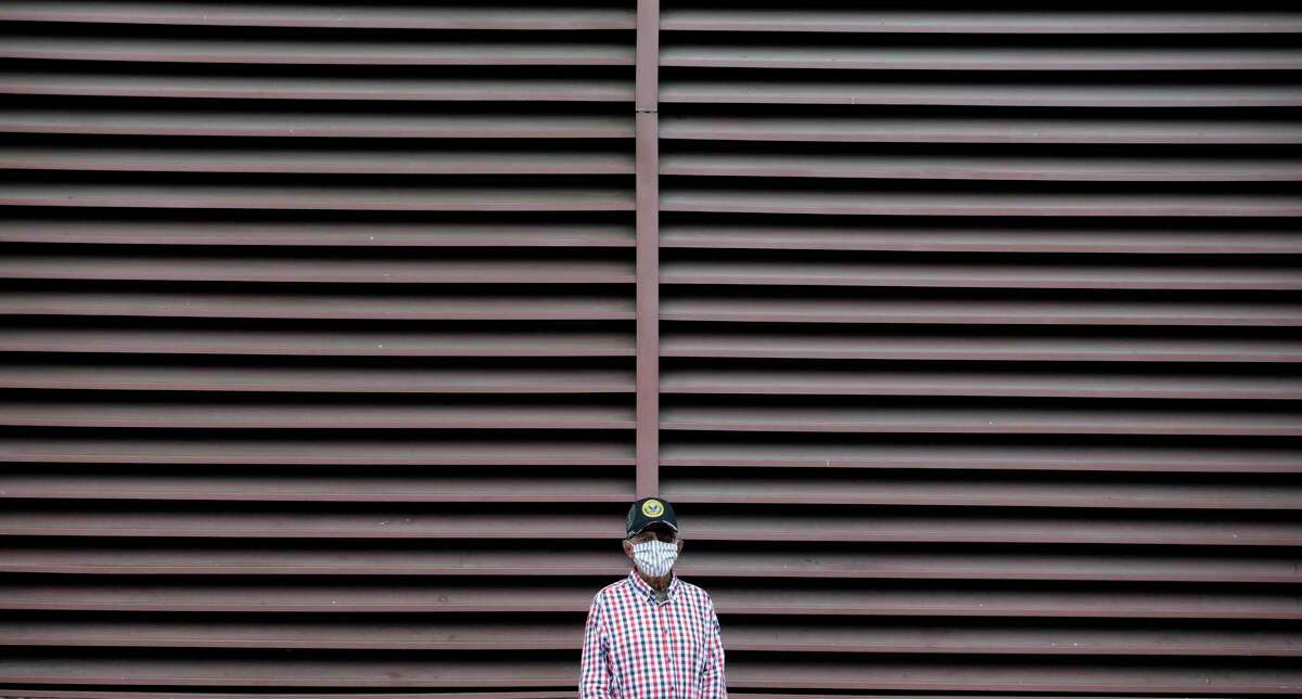 A man wears a face mask as he waits for a bus in San Antonio on Wednesday. VIA bus drivers are asking for a 20 percent hazard pay raise for working during the coronavirus pandemic. (AP Photo/Eric Gay)