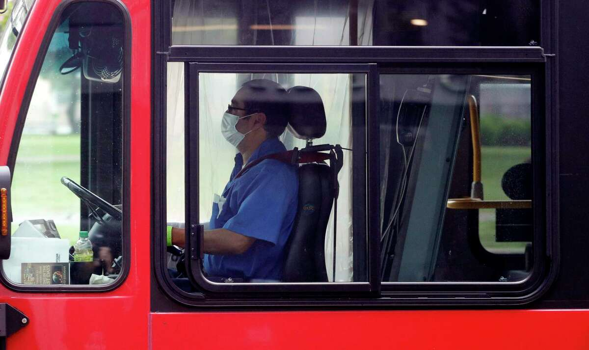 A bus driver wears a face mask and is sits behind a plastic curtain as he drives a VIA bus in San Antonio on Wednesday. VIA Metropolitan Transit has gone to a