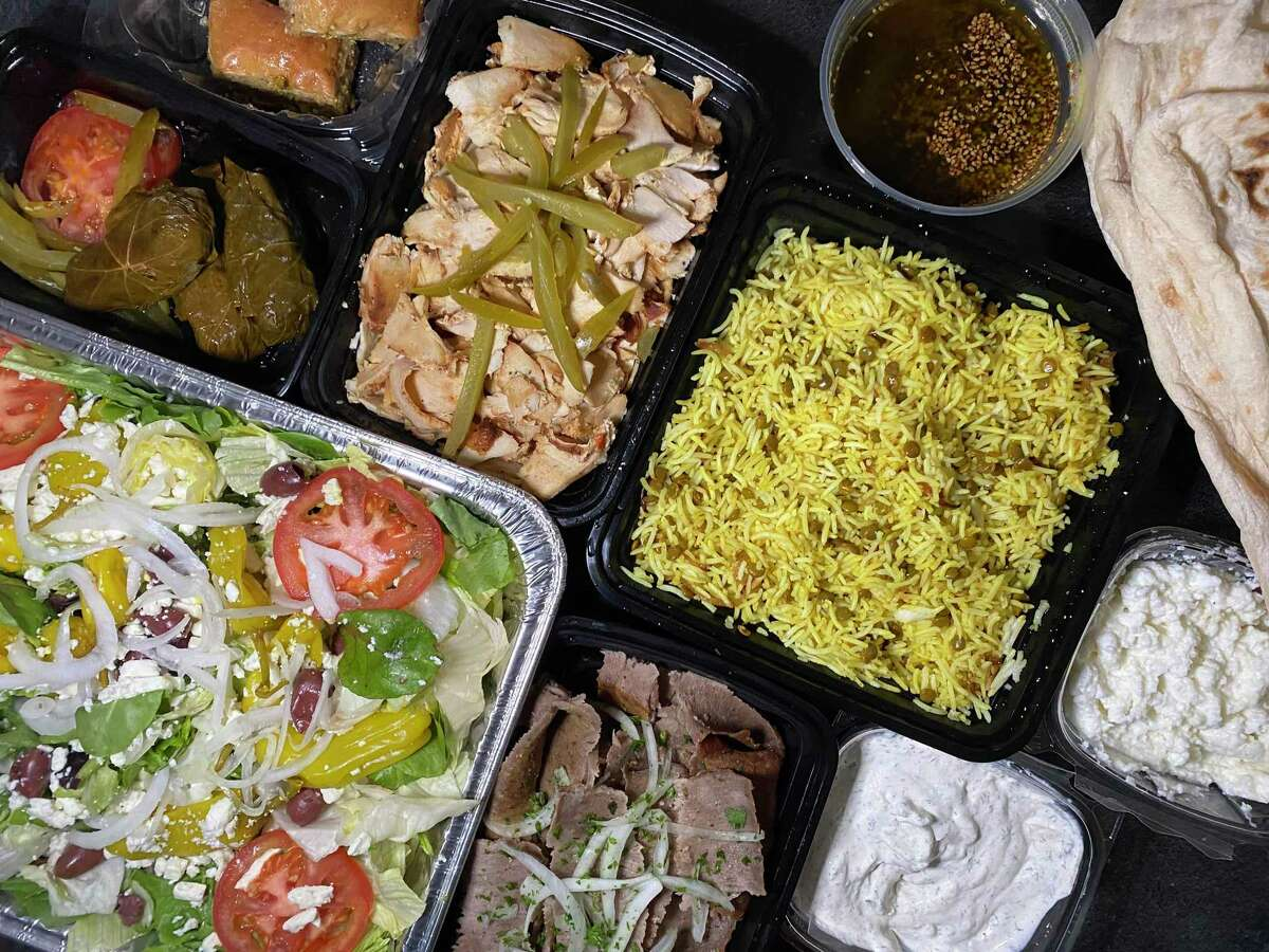 A family pack of Mediterranean food to-go includes, clockwise from bottom left, Greek salad, dolma (additional charge), baklava, chicken shawarma, lentil rice, fresh pita, garlic sauce, tzatziki and gyro meat with beef and lamb from Pasha Mediterranean Grill on Wurzbach Road.