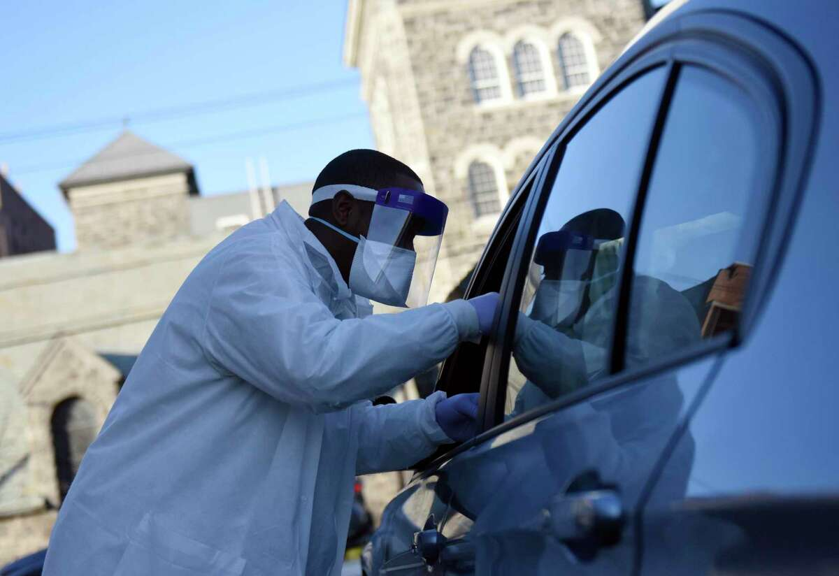 Phlebotomist Warren Dawkins demonstrates drive-thru testing for coronavirus at Murphy Medical Associates in Greenwich, Conn. Monday, March 9, 2020.