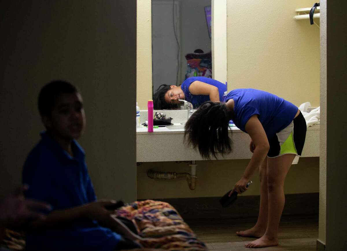 La'Keisha Lawrence, 11, brushes her hair as her 6-year-old brother Na'Kahi looks for something to watch on YouTube.