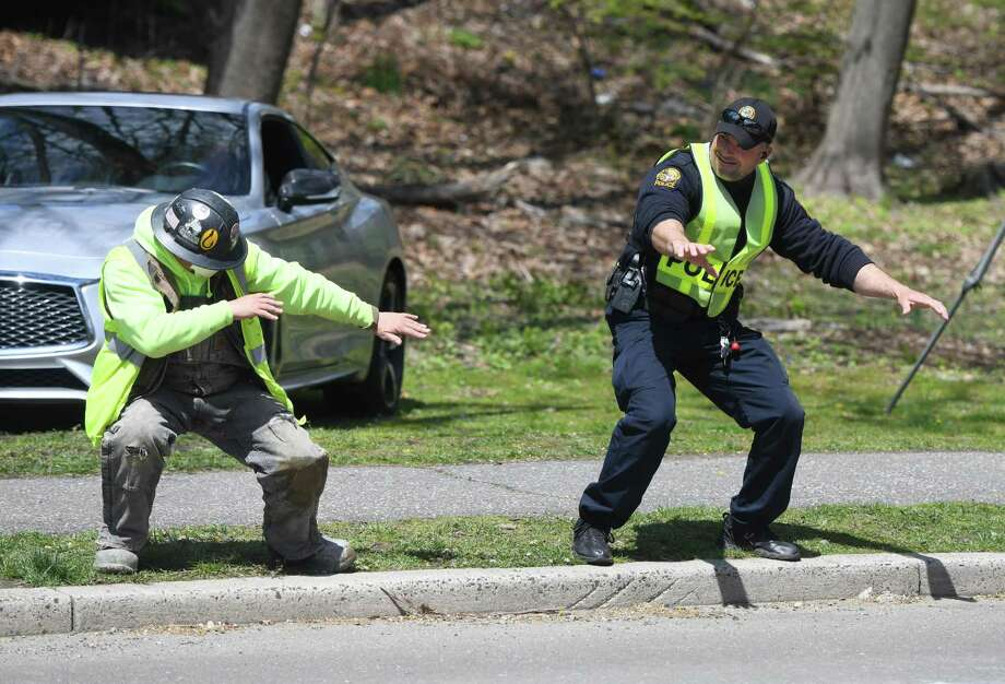 "Greenwich Police Officer ""Rockin'"" Robert Smurlo, right, dances with construction worker Cesar Guzman near Bruce Park in Greenwich, Conn. Wednesday, April 22, 2020. Officer Smurlo has been dancing to music while directing traffic to put smiles on the faces of passers by. Photo: Tyler Sizemore / Hearst Connecticut Media / Greenwich Time"