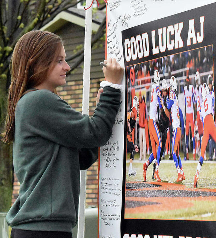 Edwardsville High School graduate Lizzie Anderson signs a banner wishing AJ Epenesa good luck on the NFL Draft on Thursday morning in Glen Carbon. Epenesa is expected to be selected in the first or second round. Photo: Matt Kamp|The Intelligencer