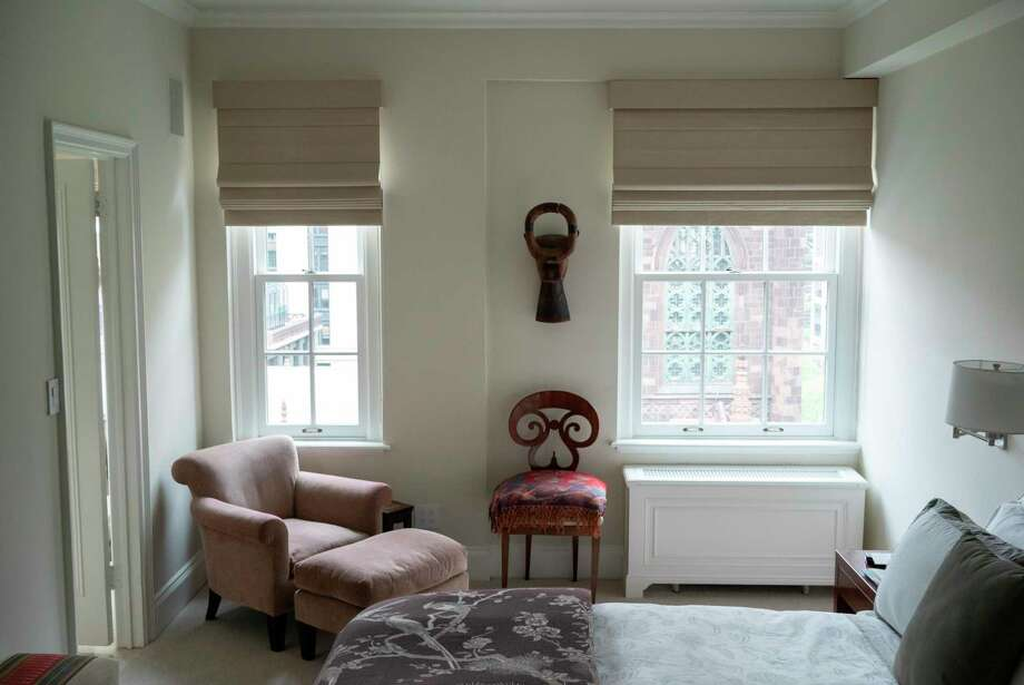 This photo provided by interior designer Carolyn DiCarlo shows a bedroom designed by DiCarlo in New York. DiCarlo created the serene bedroom for the client by combining soft colors, the harmonic forms of African art and a Biedermeier chair, and a cozy reading chair by the window that is bathed in gentle afternoon light. (Adam DiCarlo/Carolyn DiCarlo via AP) Photo: Adam DiCarlo / Adam DiCarlo/Associated Press / Carolyn DiCarlo