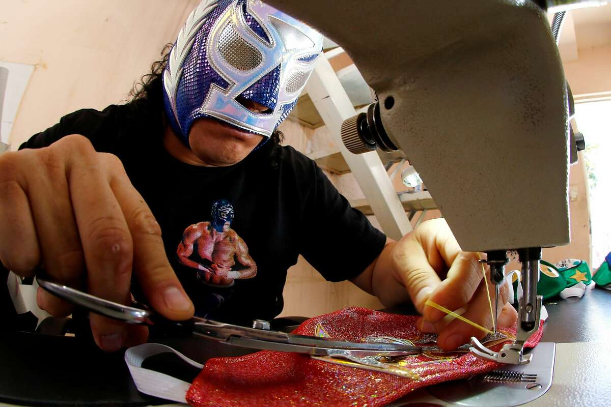 TORREON, MEXICO - APRIL 21: Mexican Lucha Libre wrestler, 'El Hijo del Soberano' makes face masks on April 21, 2020 in Torreon, Mexico. Due to the COVID-19 pandemic, 'El Hijo del Soberano' turned to produce themed protective masks in a studio with his family. (Photo by Armando Marin/Jam Media/Getty Images)