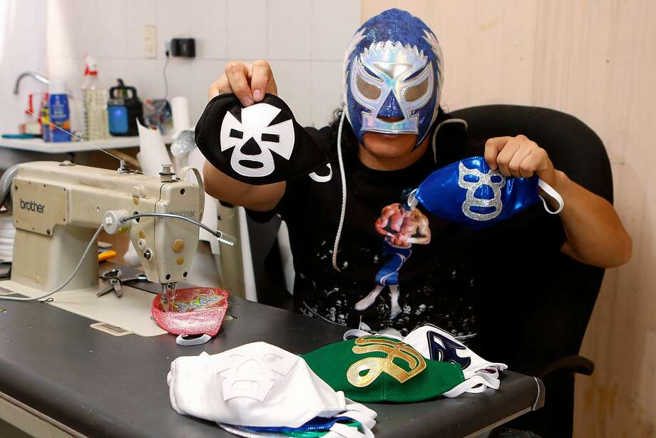 """TORREON, MEXICO - APRIL 21: Mexican Lucha Libre wrestler, 'El Hijo del Soberano' shows a 'Blue Demon' and """"El Espanto"""" wrestlers face masks on April 21, 2020 in Torreon, Mexico. Due to the COVID-19 pandemic, 'El Hijo del Soberano' turned to produce themed protective masks in a studio with his family. (Photo by Armando Marin/Jam Media/Getty Images) Photo: Jam Media/Getty Images / 2020 Jam Media"""