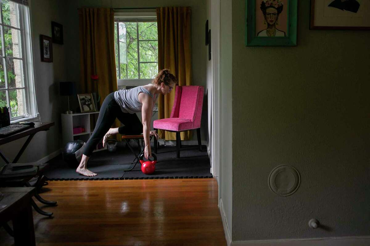 Katie King has created a special area in her home where she practices yoga and does CrossFit exercises to help reduce the stress of living alone in a time of stay-at-home orders.