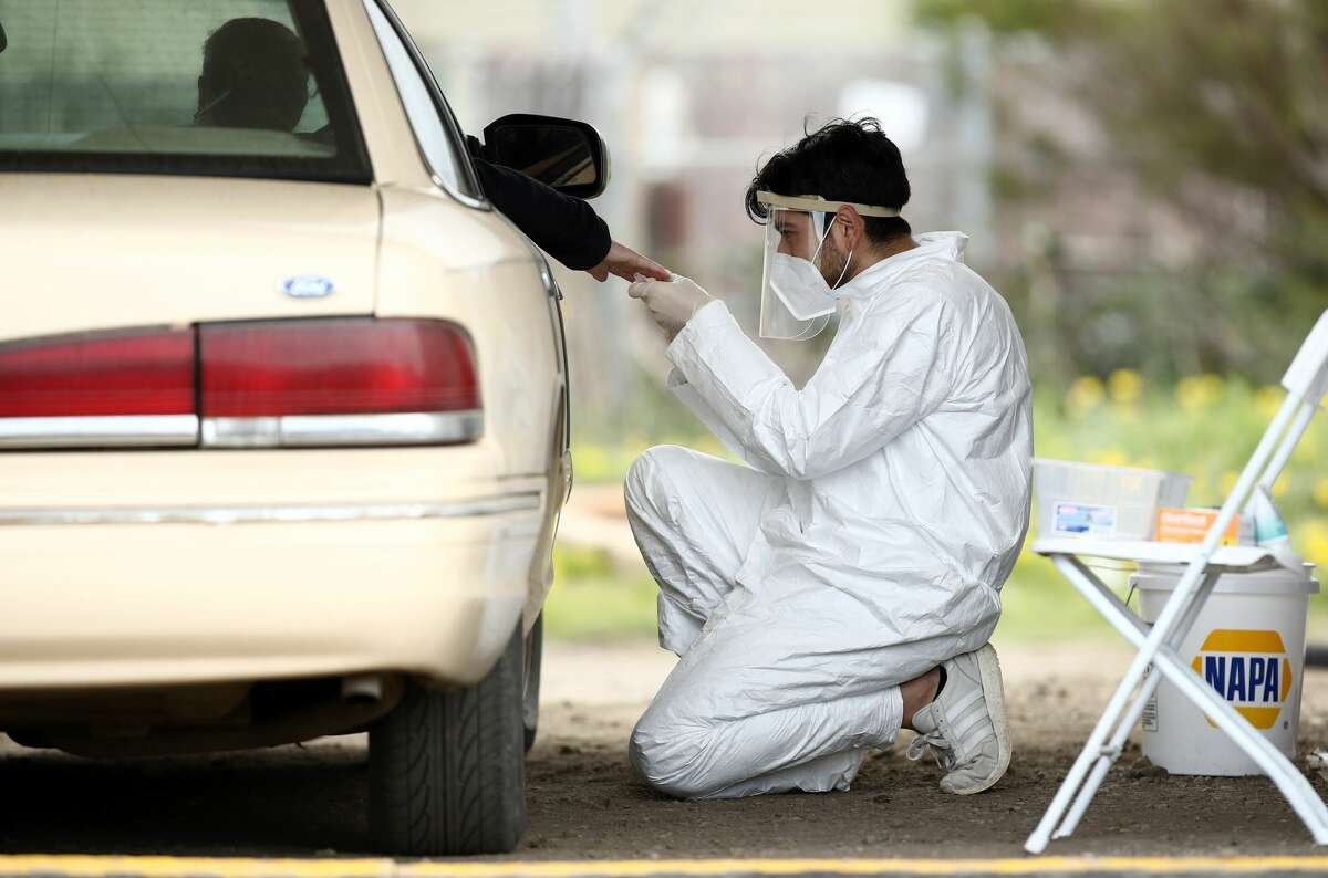 A medical professional administers a coronavirus (COVID-19) test at a drive thru testing location conducted by staffers from University of California, San Francisco Medical Center (UCSF) in the parking lot of the Bolinas Fire Department April 20, 2020 in Bolinas, California.