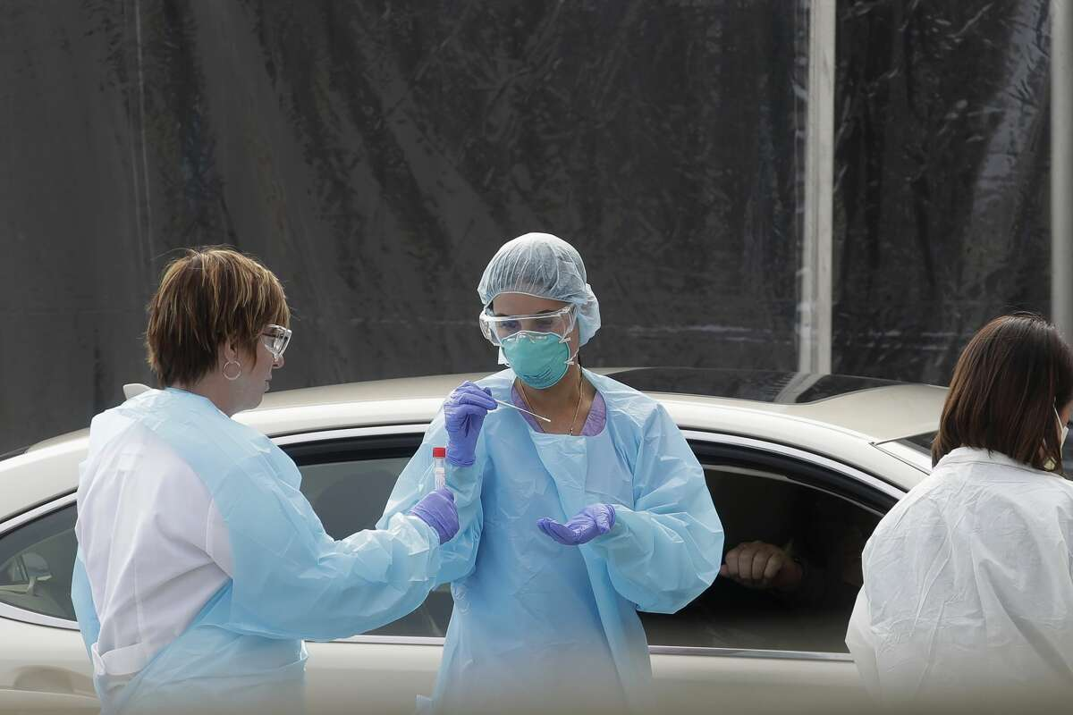 In this March 12, 2020, file photo, health care personnel test a person in the passenger seat of a car for coronavirus at a Kaiser Permanente medical center parking lot in San Francisco. California public health officials are now recommending health care workers and others in high risk settings who do not have symptoms be tested for the coronavirus. The change was outlined in a memo dated Sunday, April 19. The memo breaks with guidance from the U.S. Centers for Disease Control and Prevention, which says only those showing symptoms should be tested.