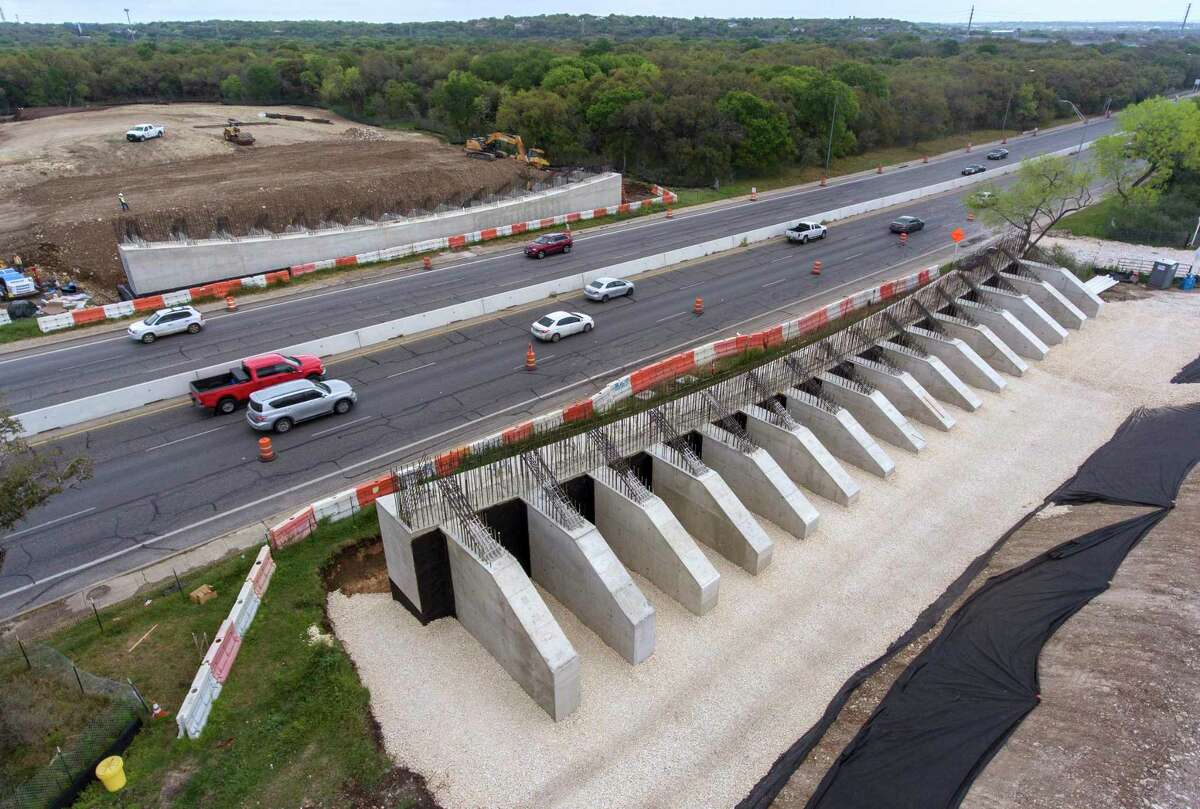Cars drive along Wurzbach Parkway and between the foundations of the future land bridge in Hardberger Park on March 17.