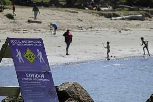 A sign reminding people to socially distance six feet is seen Wednesday, April 22, 2020, at Crab Cove in Alameda, Calif. Law enforcement officers say they could start writing tickets today to people who aren't wearing masks in public. Masks are now required in six Bay Area counties including Alameda, Contra Costa, Marin, San Francisco, San Mateo, and Sonoma.