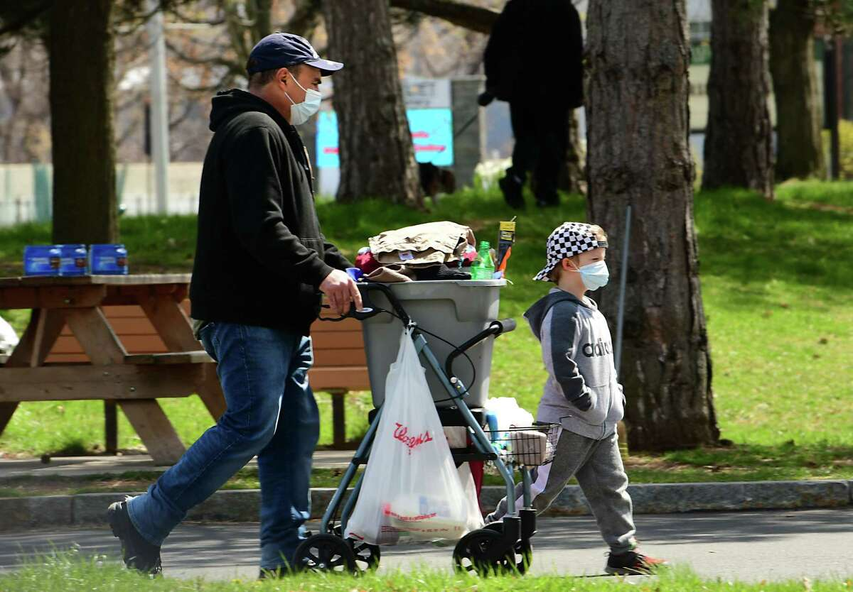 A man is seen walking with a young boy near Broadway on Thursday, April 23, 2020 in Watervliet, N.Y. During the next few weeks, the Capital Region will see rain showers.