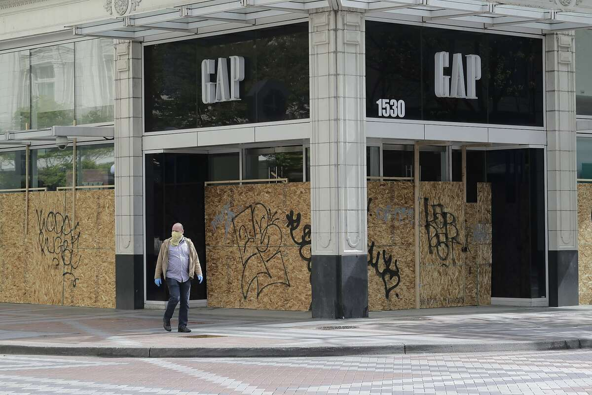 AFTER: A pedestrian wearing a mask passes a boarded up Gap store on Saturday, April 18, 2020, in downtown Seattle. Streets remained mostly empty due to Washington state's ongoing stay-at-home order and non-essential businesses continuing to be closed as a result of the outbreak of the coronavirus.