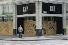 A pedestrian wearing a mask passes a boarded up Gap store, Saturday, April 18, 2020, in downtown Seattle. Streets remained mostly empty due to Washington state's ongoing stay-at-home order and non-essential businesses continuing to be closed as a result of the outbreak of the coronavirus. (AP Photo/Ted S. Warren)
