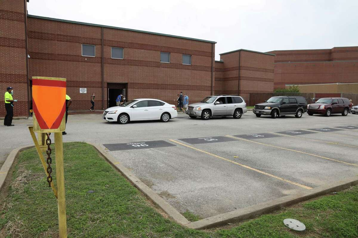 Parents line up in their vehicles at the Katy Independent School District's Education Support Complex on Wednesday, April 22, to receive technology devices like laptops, tablets and hot spots, which will help them educate their students as schools remain closed through the academic year.