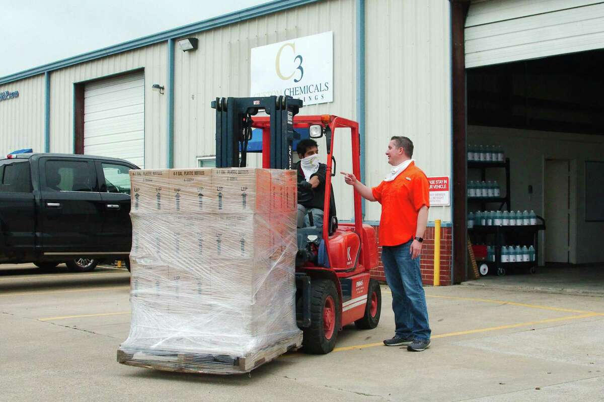 McAllister speaks to employee Daniel Sosa, who is moving a pallet of hand sanitizer at the Pearland company.