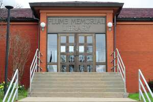 Signs notify patrons of the closure of Plumb Memorial Library due to the coronavirus in Shelton, Conn., on Wednesday Apr. 8, 2020. A plush toy bear sits in the front window to greet passers-by.