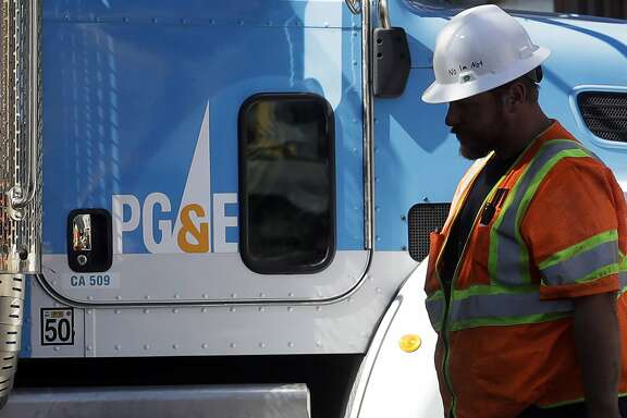 FILE - In this Aug. 15, 2019, file photo, a Pacific Gas & Electric worker walks in front of a truck in San Francisco. PG&E and California Gov. Gavin Newsom have reached a deal for the nation's largest utility to emerge from bankruptcy triggered by massive liabilities from wildfires. PG&E agreed to overhaul its board and operations and to put the company up for sale if it doesn't get out of bankruptcy by June 30. (AP Photo/Jeff Chiu, File)