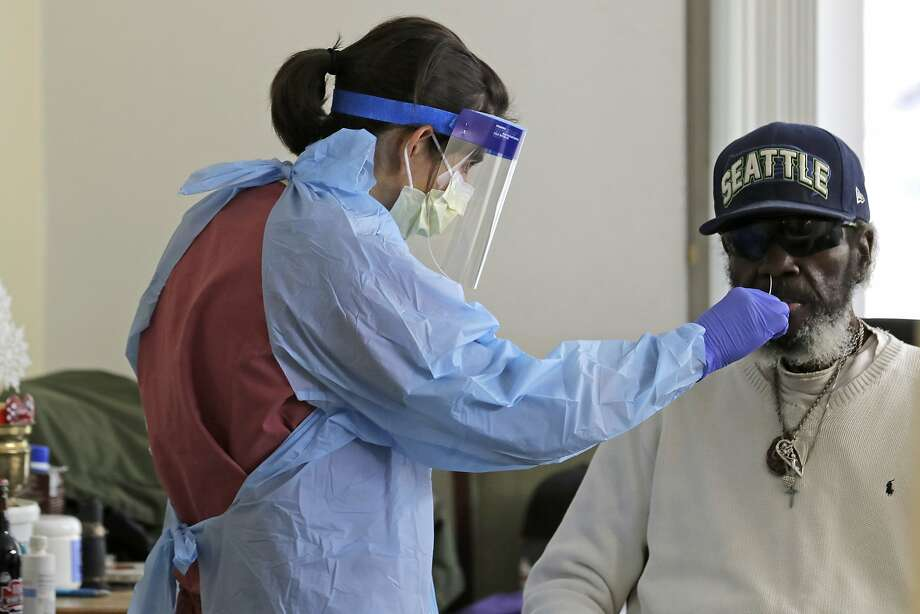"""In this April 17, 2020, photo, Dr. Gabrielle Beger, left, takes a nose-swab sample from Lawrence McGee, right, as she works with a team of University of Washington medical providers conducting testing for the new coronavirus at Queen Anne Healthcare, a skilled nursing and rehabilitation facility in Seattle. More than 100 residents were tested during the visit, and the results for all were negative, according to officials. Sending """"drop teams"""" from University of Washington Medicine to conduct universal testing at skilled nursing facilities in collaboration with public health officials is one aspect of the region's approach to controlling the spread of the coronavirus. (AP Photo/Ted S. Warren) Photo: Ted S. Warren, Associated Press"""