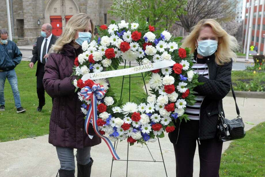 Sisters Patti Charette, left, and Paula Gill carry a wreath to be placed at the L'Ambiance Plaza memorial in Bridgeport, Conn. April 23, 2020. Their father, Richard McGill, was one of 28 workers killed in the 1987 construction accident. The sisters volunteered to place a wreath at the memorial this year since the anniversary remembrance ceremony was not held due to the pandemic. Photo: Ned Gerard / Hearst Connecticut Media / Connecticut Post