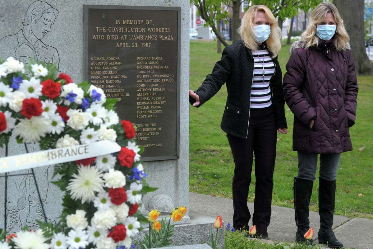 Sisters Paula Gill, left, and Patti Charette, stand next to the L'Ambiance Plaza memorial during a moment of silence in Bridgeport, Conn. April 23, 2020. Their father, Richard McGill, was one of 28 workers killed in the 1987 construction accident. The sisters volunteered to place a wreath at the memorial this year since the anniversary remembrance ceremony was not held due to the pandemic.