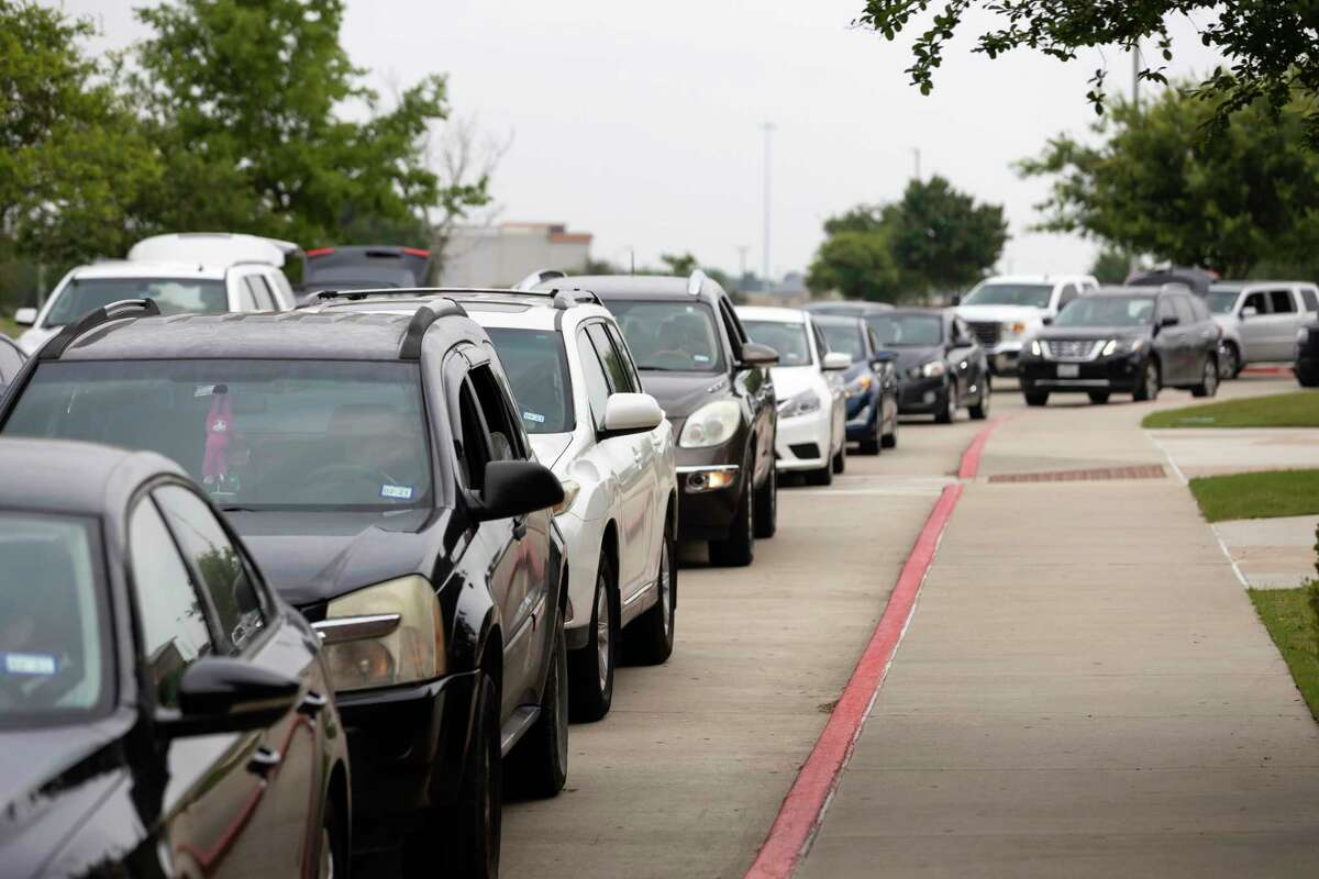 Vehicles line up as they await their turn to receive receive during a weekly mega food distribution event at the Houston Premium Outlets in Cypress, Wednesday, April 22, 2020. The vehicle line began forming early in the morning and spanned approximately 2.5 miles long.