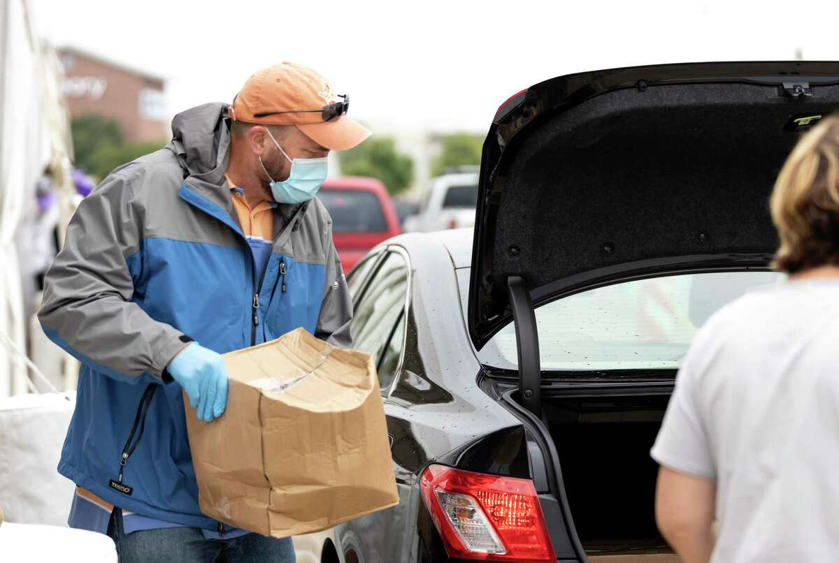 Nathan Crowell takes a prepped boxed food package to the back of a car at the Houston Premium Outlets in Cypress, Wednesday, April 22, 2020. The Houston Food Bank, in partnership with Cy-Hope hosted a mega weekly food distribution event that assisted over 6,000 families.