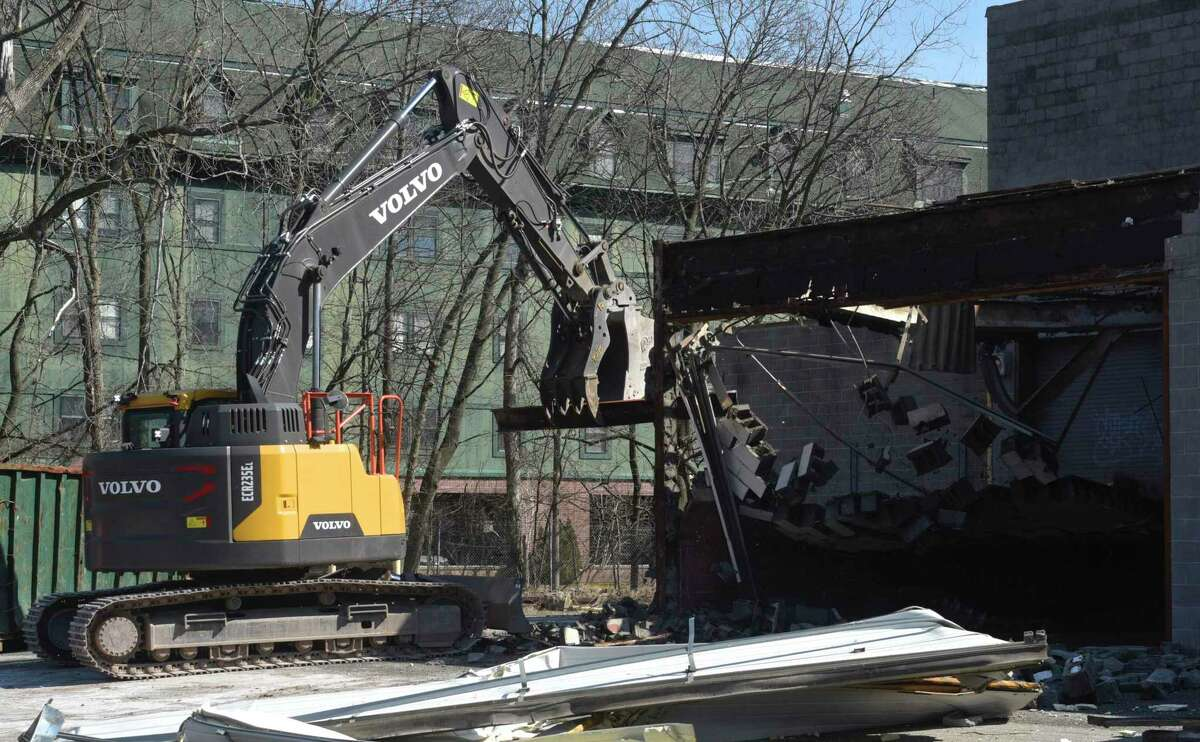 An excavator knocks down a wall during demolition work on the former News Times building at 333 Main Street in Danbury, Conn. Monday, March 2, 2020.